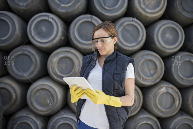 Worker woman with barrel background and work clothes. Protective glasses and gloves.