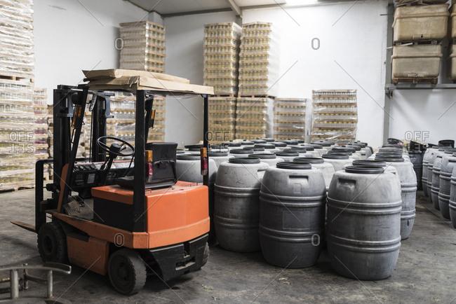 Forklift and barrels in factory warehouse. Olives fermenting in barrels