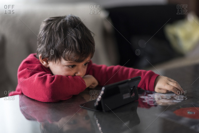 Young boy looking smartphone at home in home living room