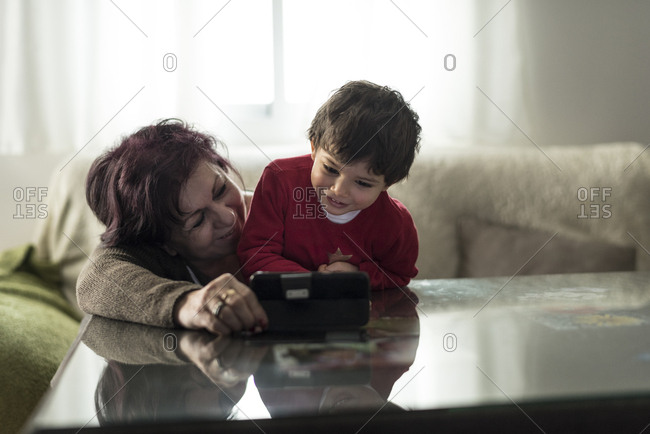 Grandmother and grandson looking smartphone at home in home living room