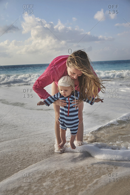 Seven month old baby with mom on beach