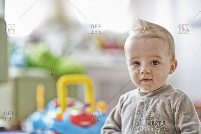 Seven month old baby boy in PJ's looking at camera in playroom