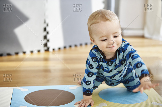 Eight month old baby boy in PJ's crawling on play mat in playroom