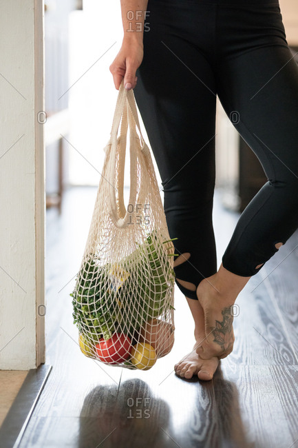 A woman in yoga pants holding a reusable shopping bag of fresh vegetables