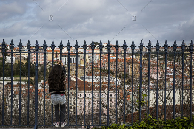 March 28, 2016: A girl plays on railings overlooking the city in Lisbon, Portugal.