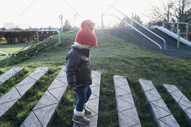 Boy walking on wooden stepping stone path