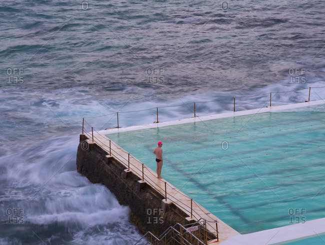Lone swimmer stands on the edge of pool by the ocean