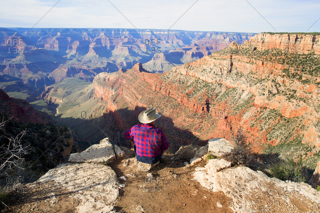 Cowboy sitting on the rim of the Grand Canyon