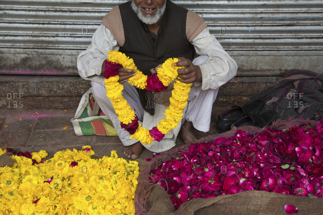 Flower seller holds out a garland of flowers in market in New Delhi, India