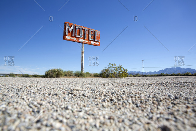 Old abandoned motel sign in Mojave desert on side of highway
