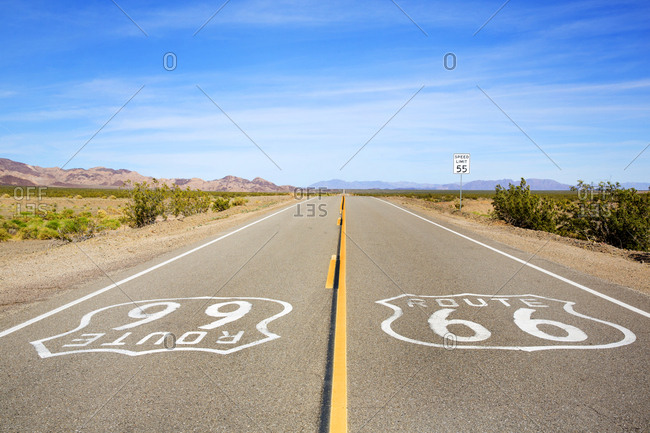 Route 66 symbols painted on asphalt as highway continues into distance