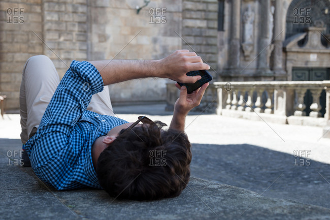 Man lying on back in open courtyard looking at mobile device