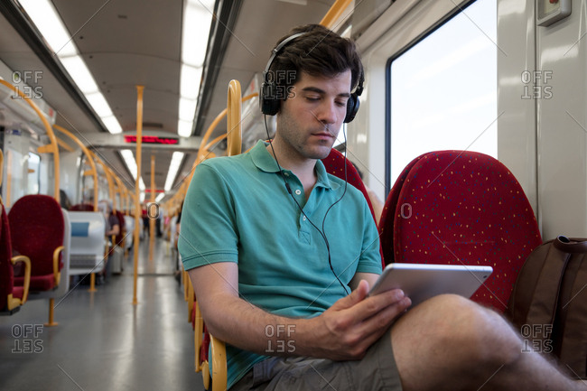 Young man riding bus watching something on tablet