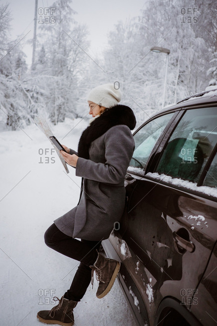 Woman studies a map in a winter forest
