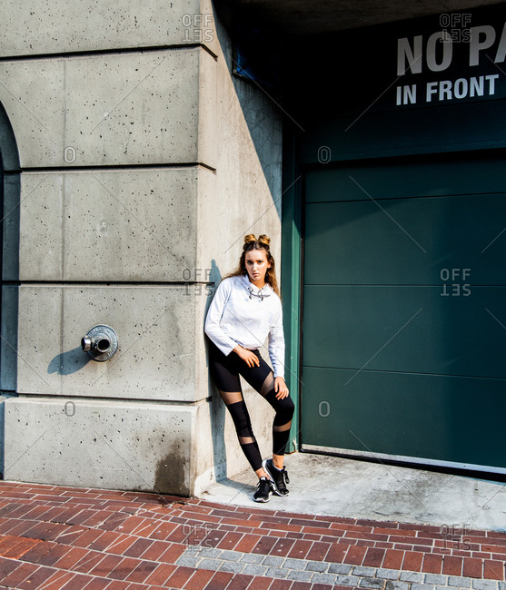 Young woman in exercise clothes leaning against wall of building