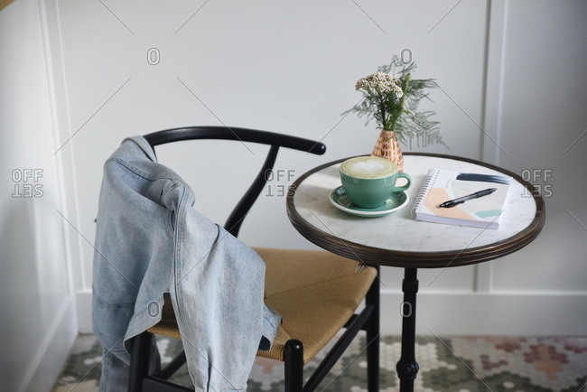 Denim jacket draped over back of chair at bistro table with coffee and notebook