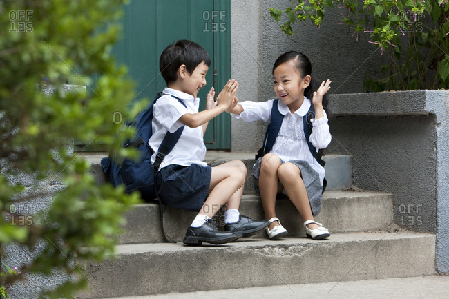 Two Chinese school children playing outside