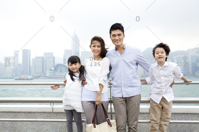 Portrait of young Chinese family in Victoria Harbor, Hong Kong