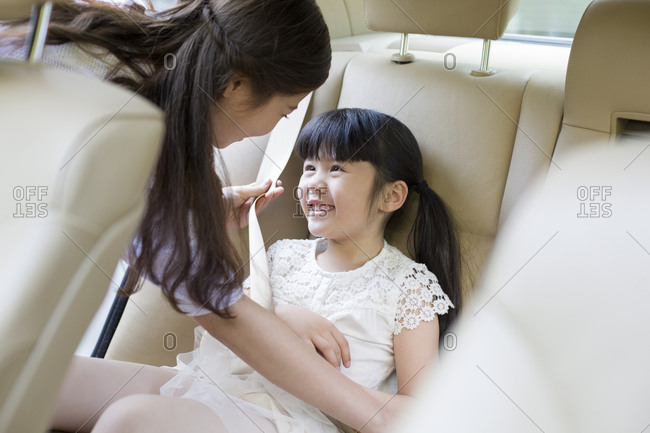 Chinese mother fastening seat belt for daughter