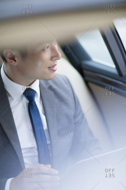 Chinese businessman sitting in car back seat