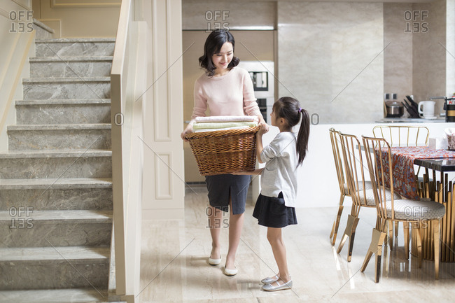 Young Chinese mother and daughter doing laundry at home