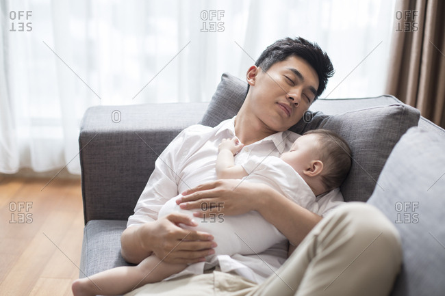 Young Chinese father and baby boy sleeping on sofa
