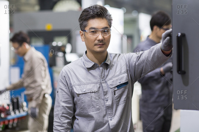 Confident Chinese engineers working in the factory