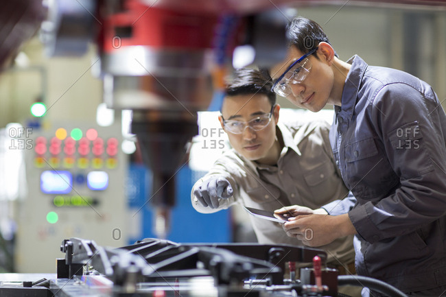 Young Chinese engineers checking machine in the factory