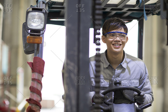 Young Chinese workman driving forklift in the factory