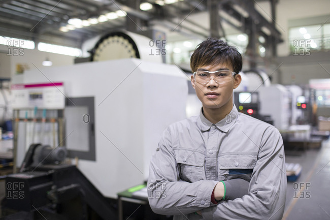 Confident Chinese engineer in the factory