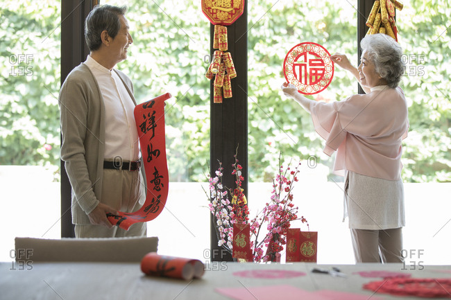 Cheerful senior couple decorating their house for Chinese New Year
