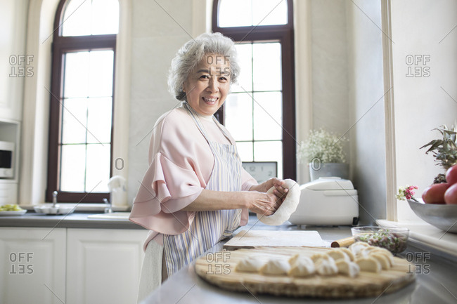 Cheerful senior Chinese woman making dumplings in kitchen