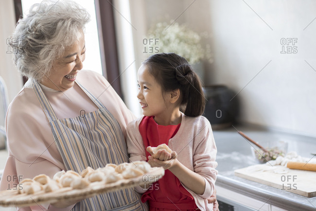 Cheerful Chinese granddaughter and grandmother making dumplings in kitchen