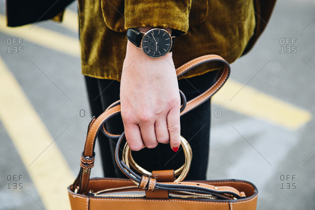 Close-up of woman standing on corner holding handbag