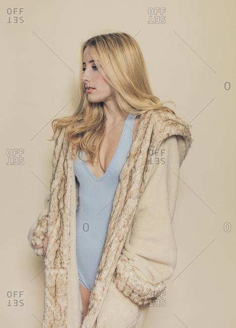 Blonde fashion model in long creamy fur coat over pastel bodysuit