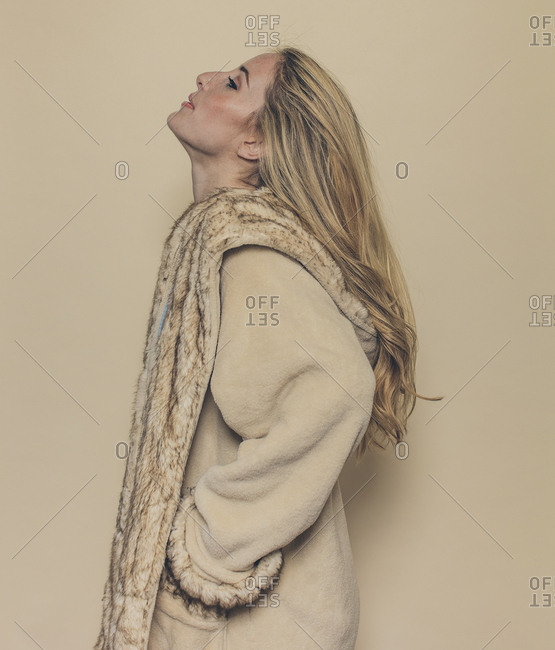 Profile of fashion model tilting head back in fur jacket