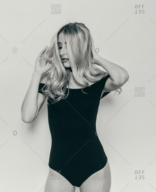 Blonde model touching her hair in black bodysuit