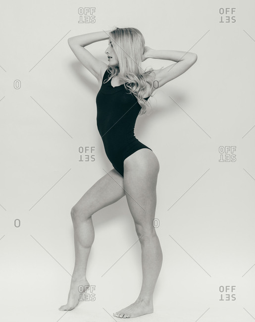 Fashion model wearing body suit standing in dance pose