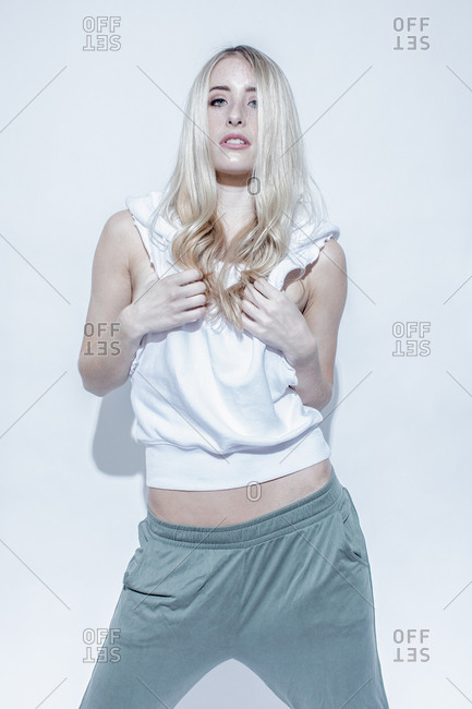 Blonde fashion model standing with legs apart pulling front of cropped sweatshirt