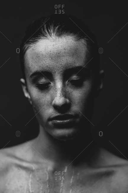 Model closing eyes with water running down face and chest