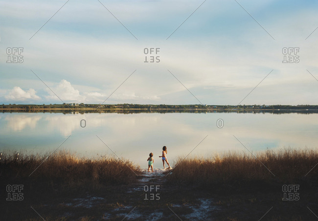 Young sisters standing  at edge of Florida lake