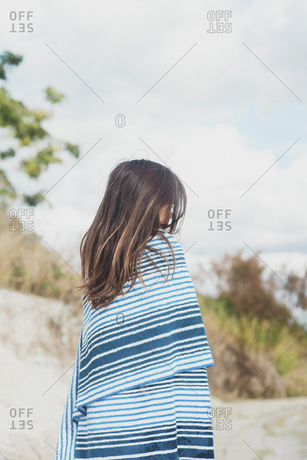 Girl wrapped in beach towel looking away