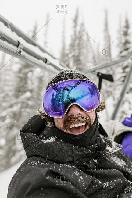 Cheerful man wearing ski goggles during winter