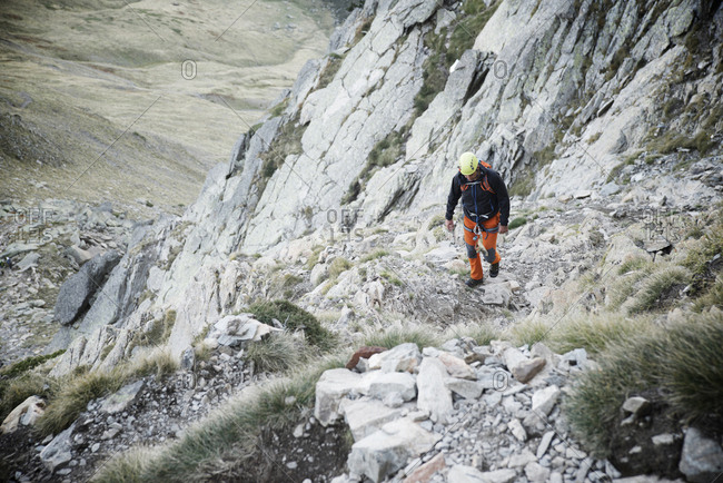 High angle view of hiker walking on rocks during mountain climbing
