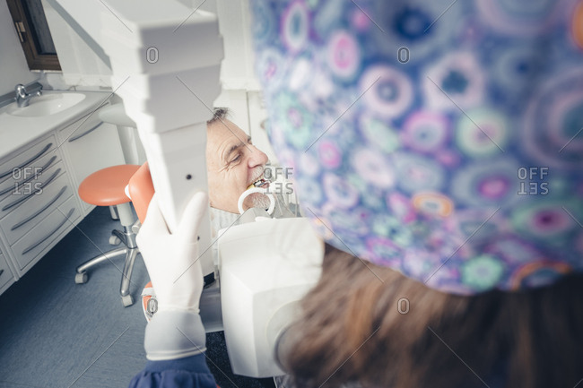 Dentist using dental equipment while examining patient's teeth