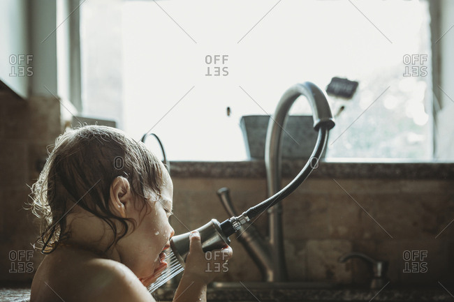 Close-up of girl playing with faucet while sitting against window in kitchen sink at home