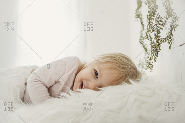 Portrait of cheerful girl lying on fur blanket at home