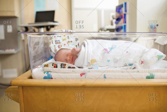 Newborn baby boy sleeping in crib at hospital