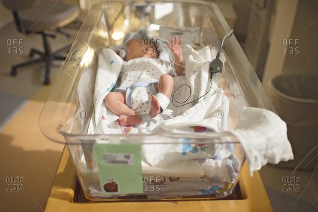 High angle view of newborn baby boy sleeping in crib at hospital