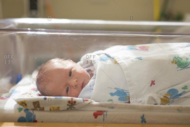 Portrait of cute newborn baby boy lying in crib at hospital
